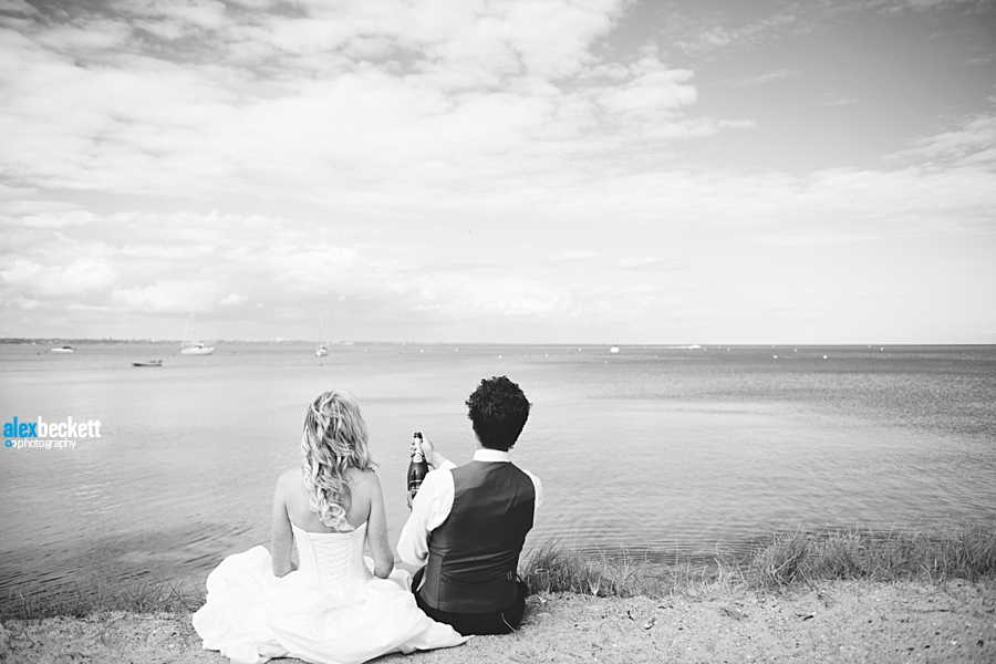 42 wedding couple at harry warren house dorset popping champagne by the sea
